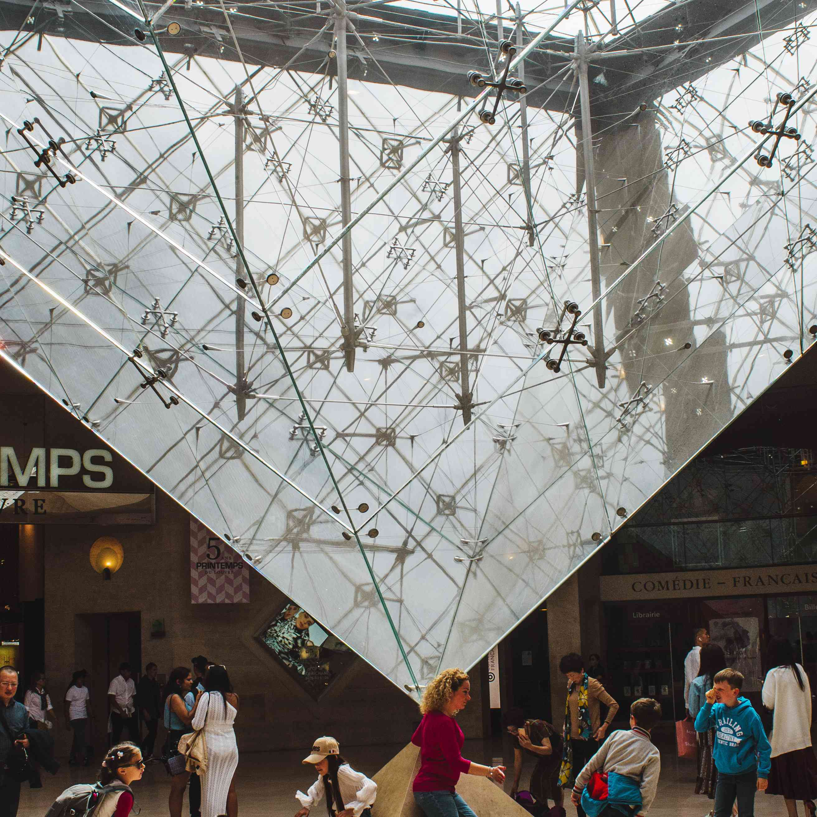 People taking photos at the bottom of the Louvre's glass pyramid