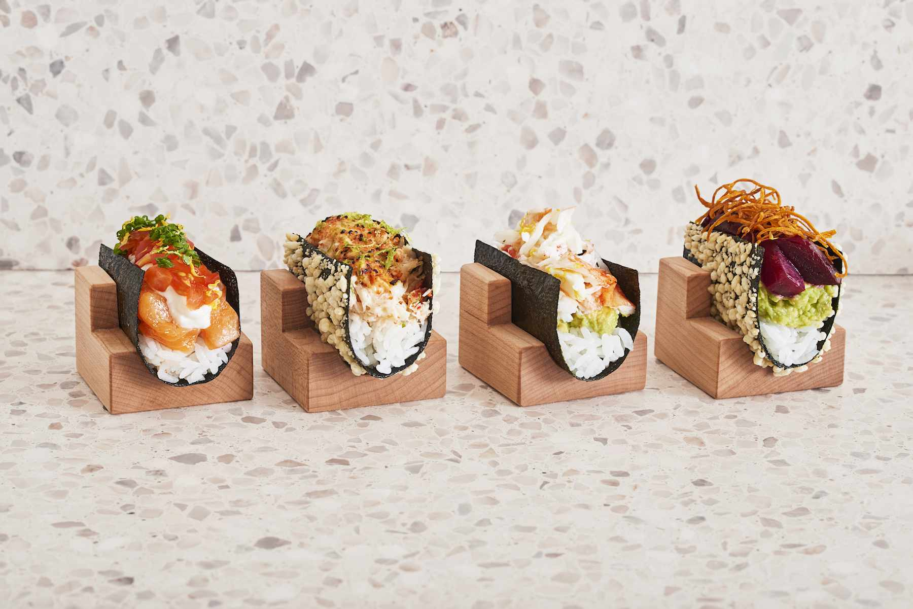 four creative sushi rolls in stands from Nami Nori