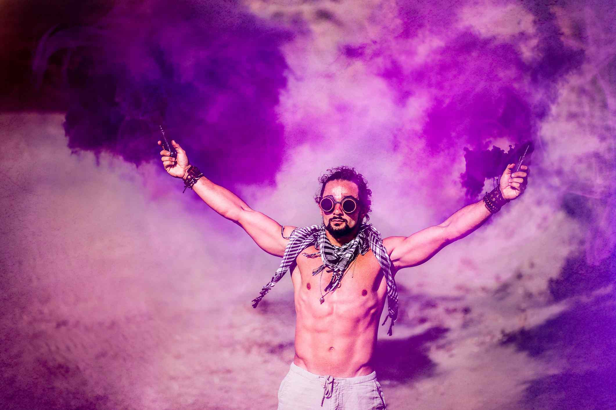 Young man standing with smoke bombs in desert
