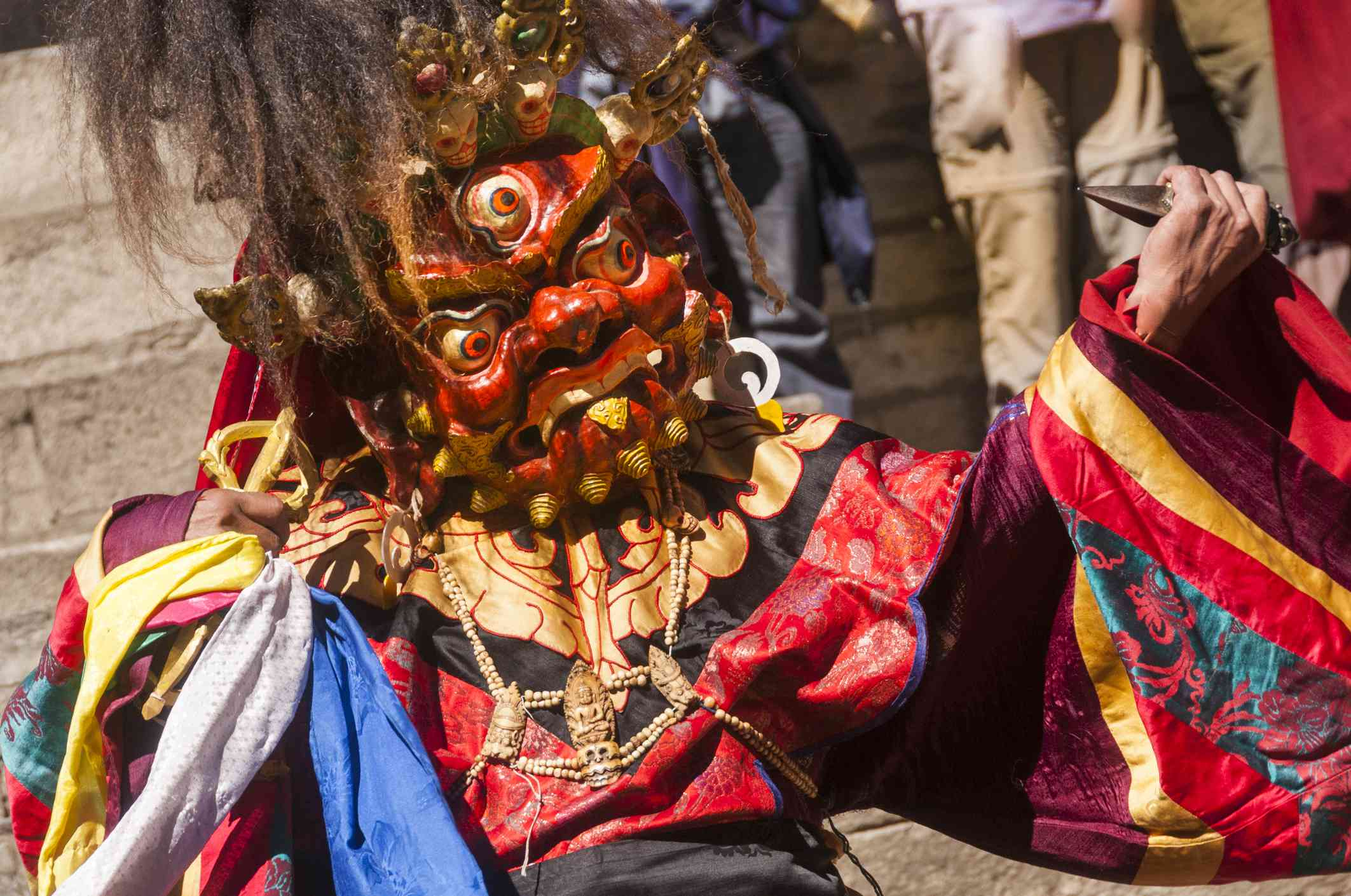 masked dancer wearing demon mask and colorful robes