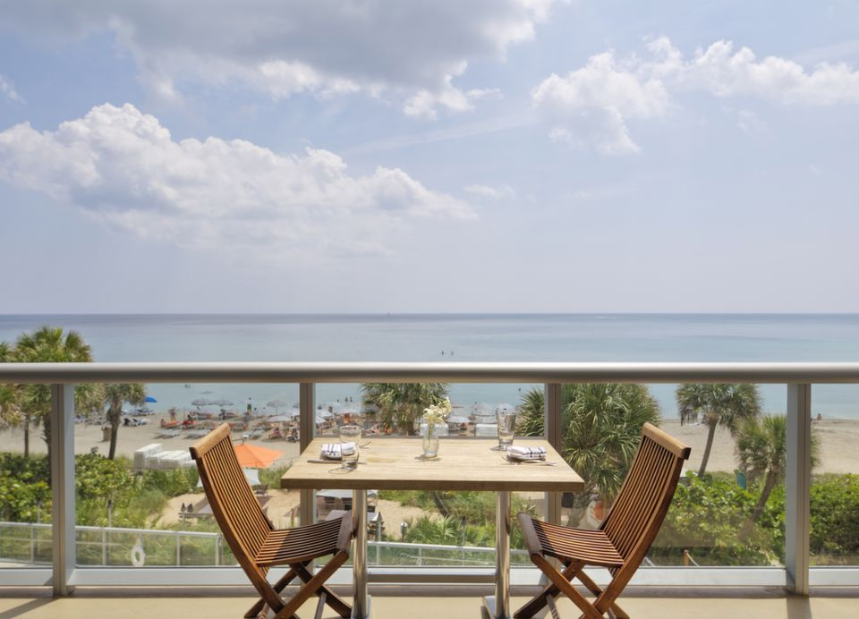 Empty table on restaurant balcony overlooking beach