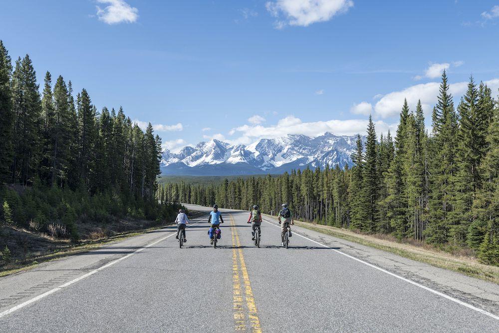 cuatro ciclistas bajan por una carretera con montañas de fondo .