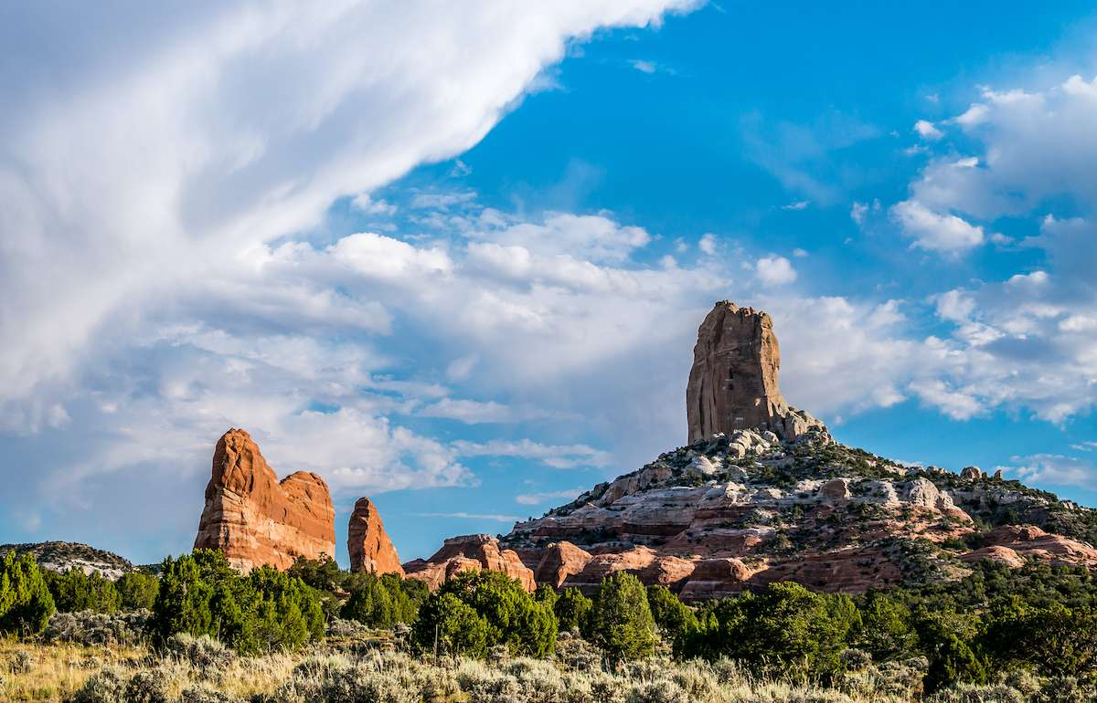 Rock formations rise from the green landscape of the Arizona desert