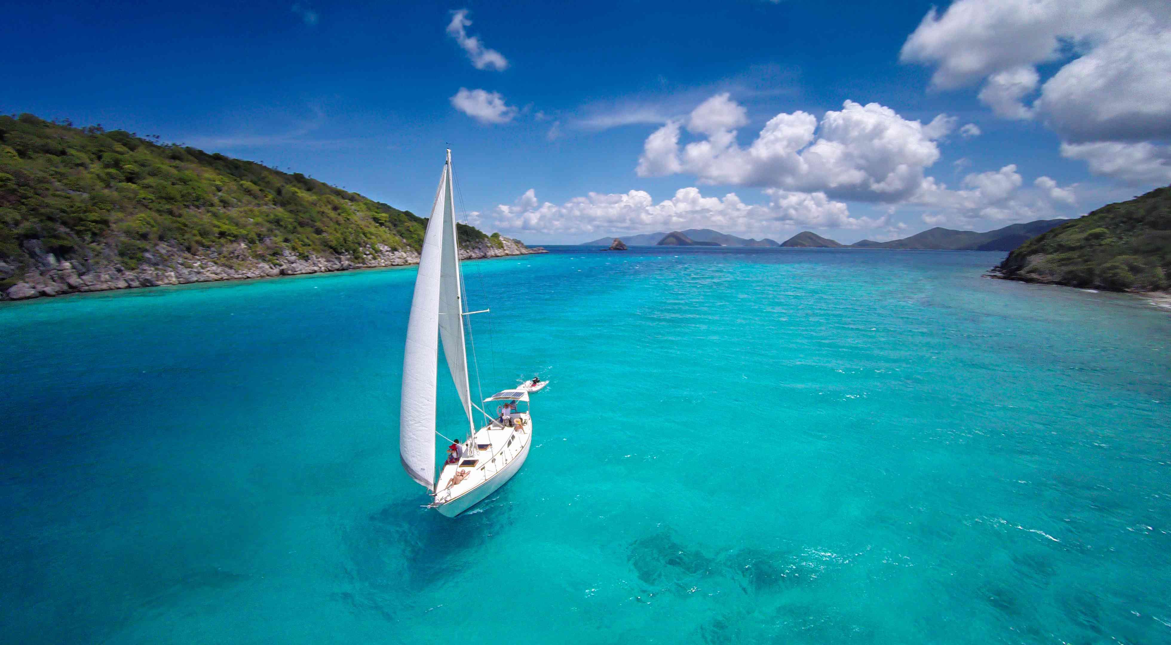aerial view of a sloop sailing through the Caribbean