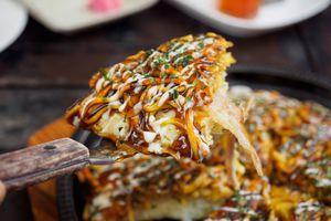 spatula holding a piece of okonomiyaki over a pan of the dish