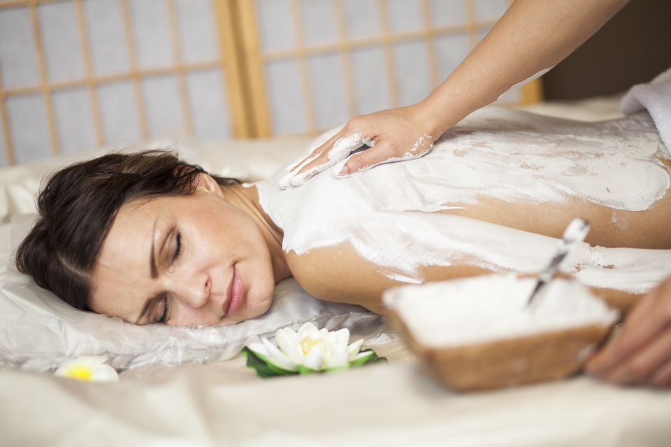 A white clay body mask being applied to a client at a spa