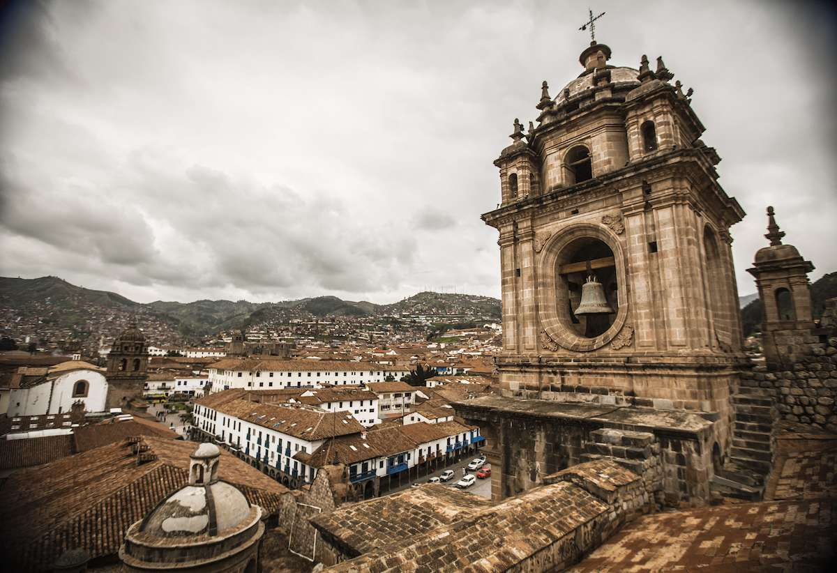 A church steeple with a bell rises above the city of Cusco