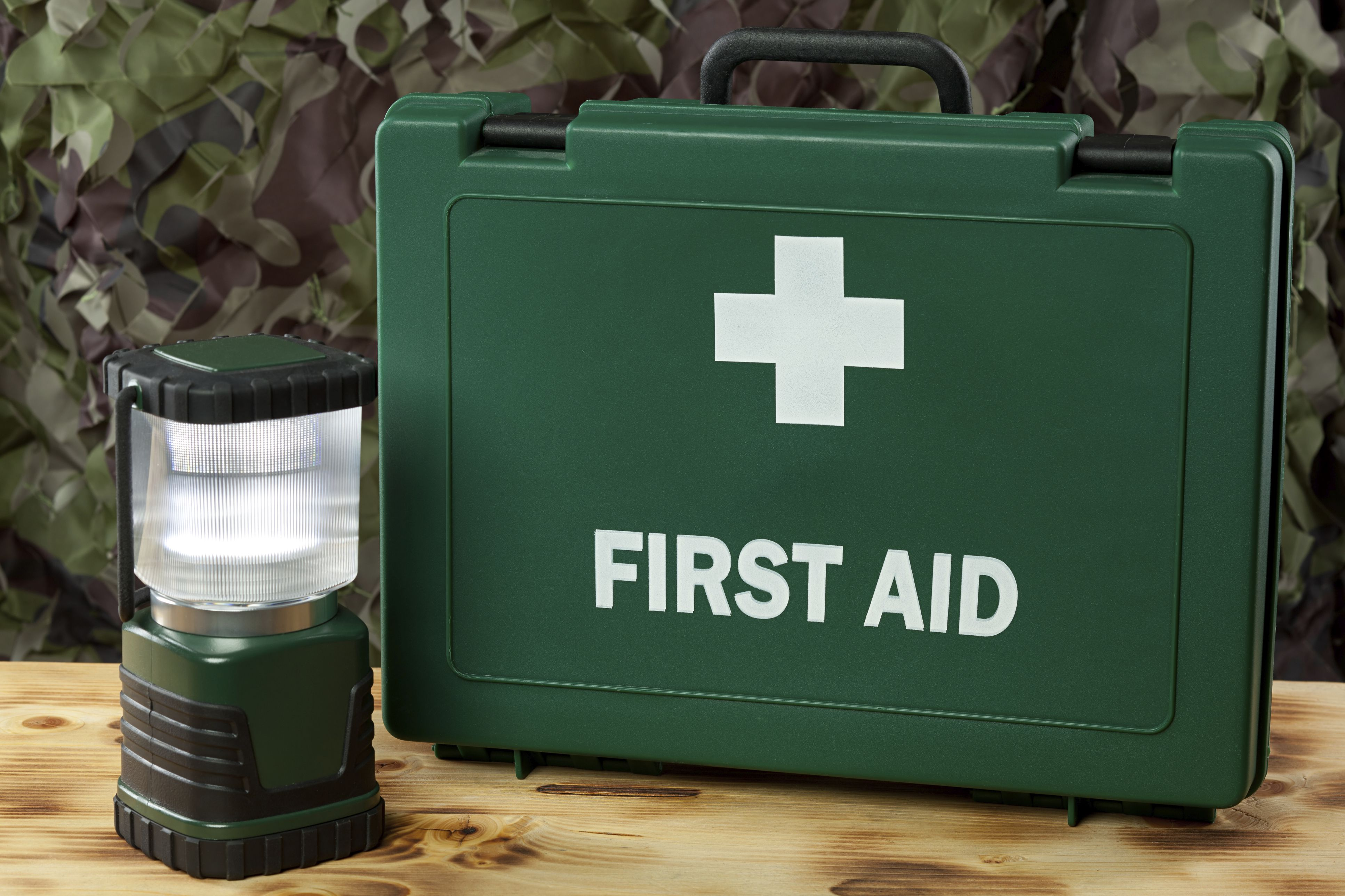 First aid kit and lantern on a table