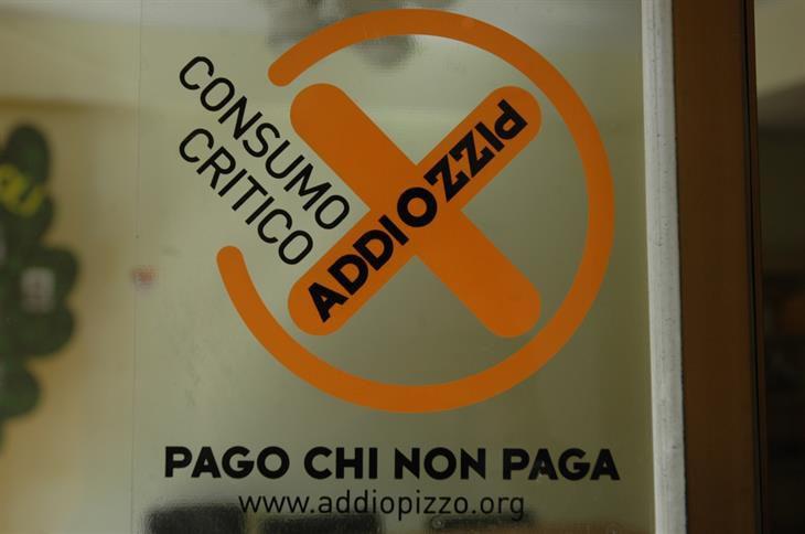 Addio Pizzo sign in a Sicilian store window