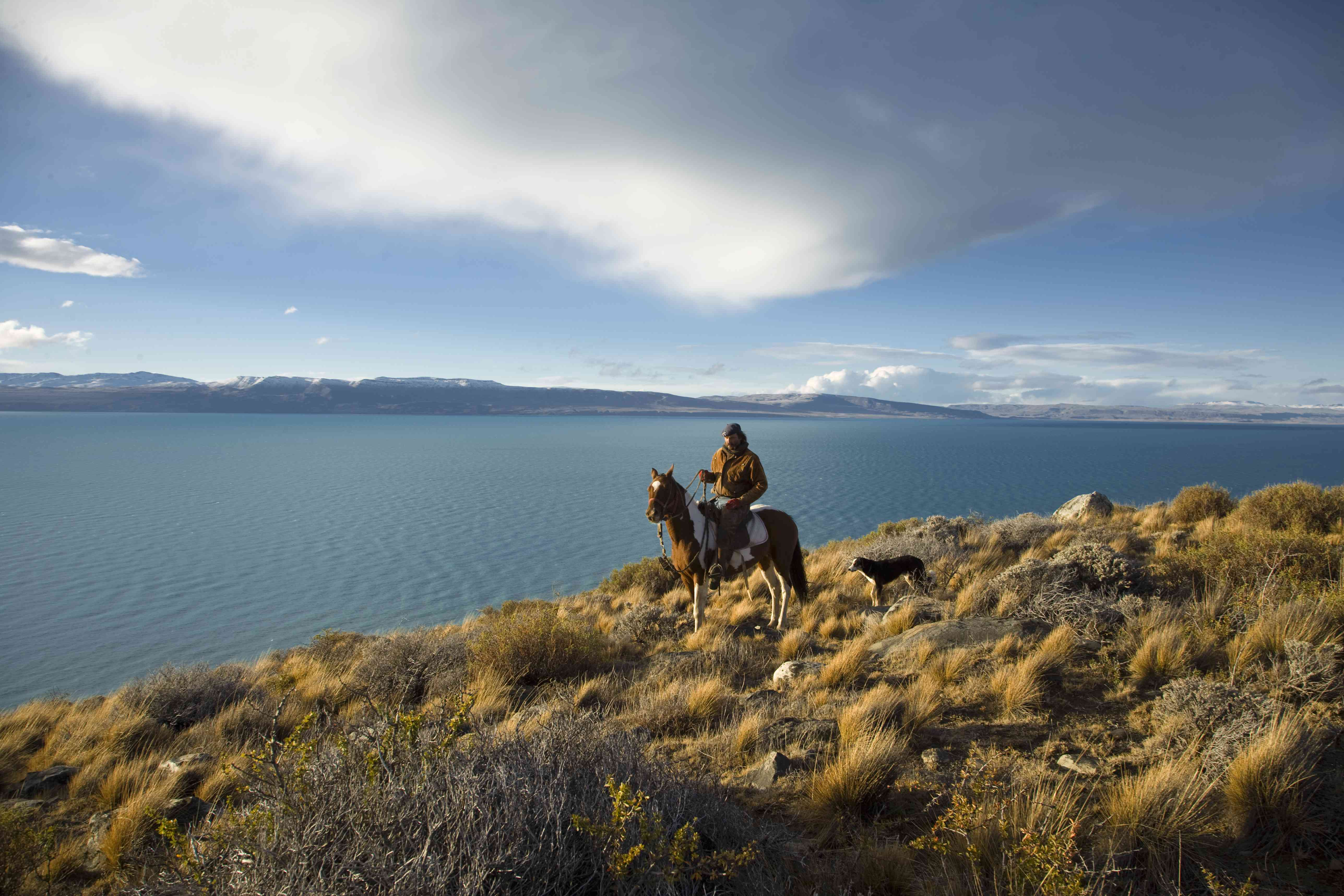 Man dressed in traditional Goucho style sitting on horse looking over Lago Argentina