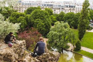 Boys sitting on rocks overlooking the view in Parc des Buttes Chaumont