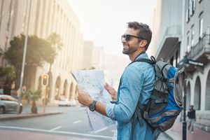 Man looking at a map while touring a foreign city