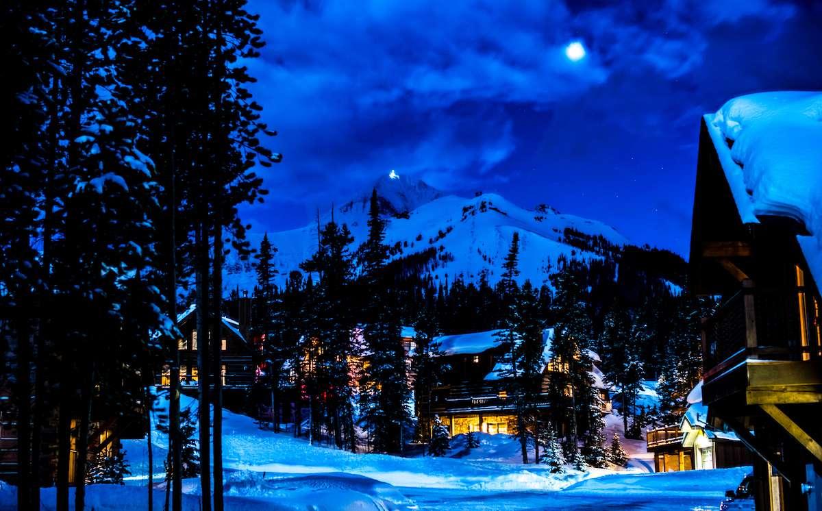 Big Sky ski resort lights up the night with a bright moon overhead.