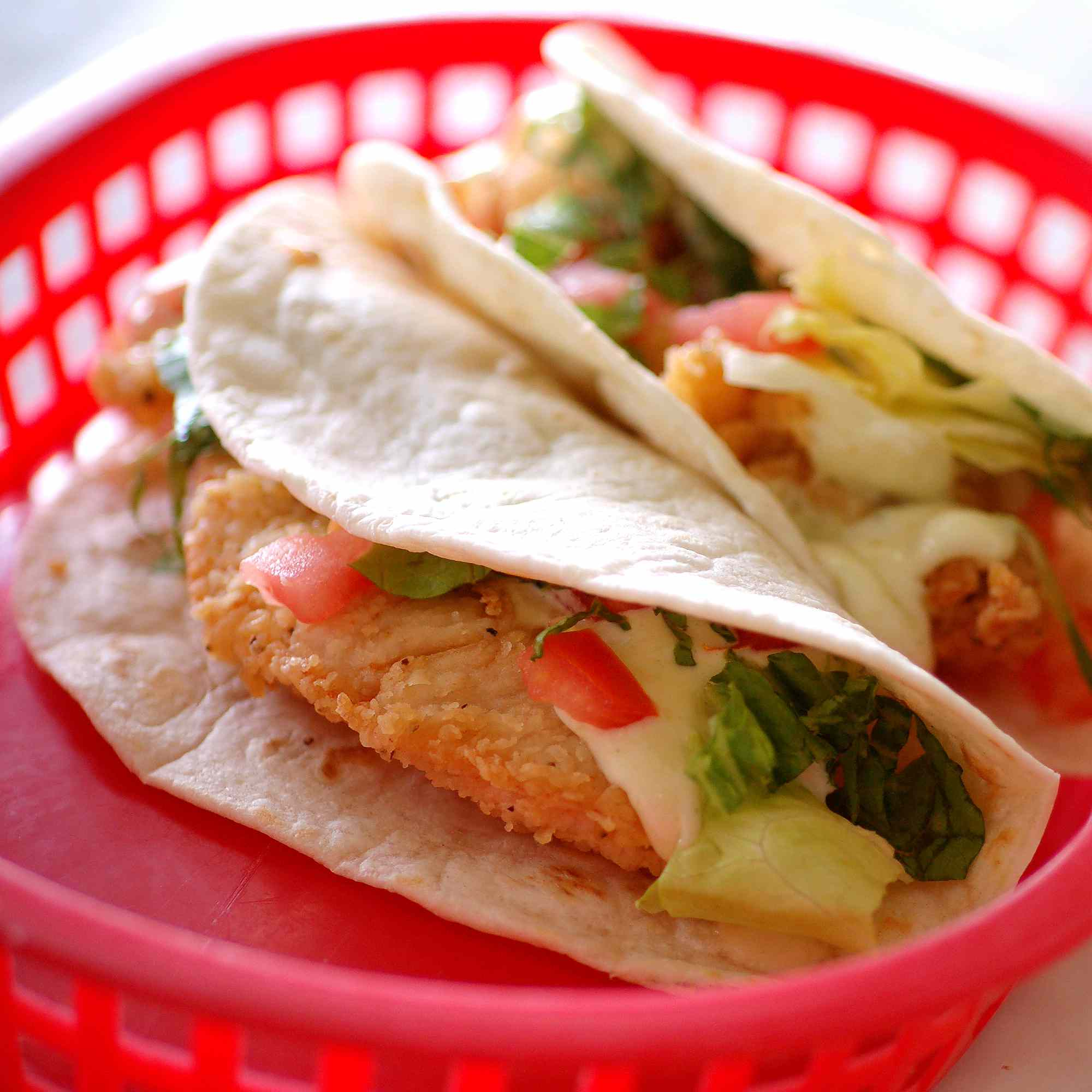 Two fish tacos in flour tortillas in a red plastic basket
