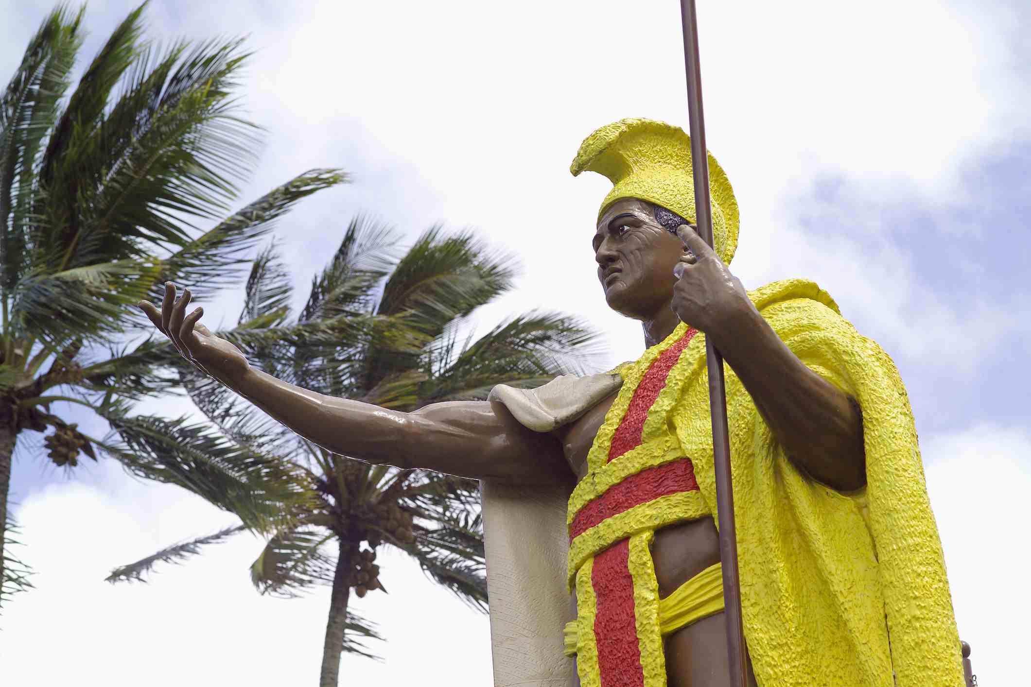 Hawaii, Big Island, North Kohala, Kapaau, Original King Kamehameha I Statue, Palm trees and cloudy blue sky