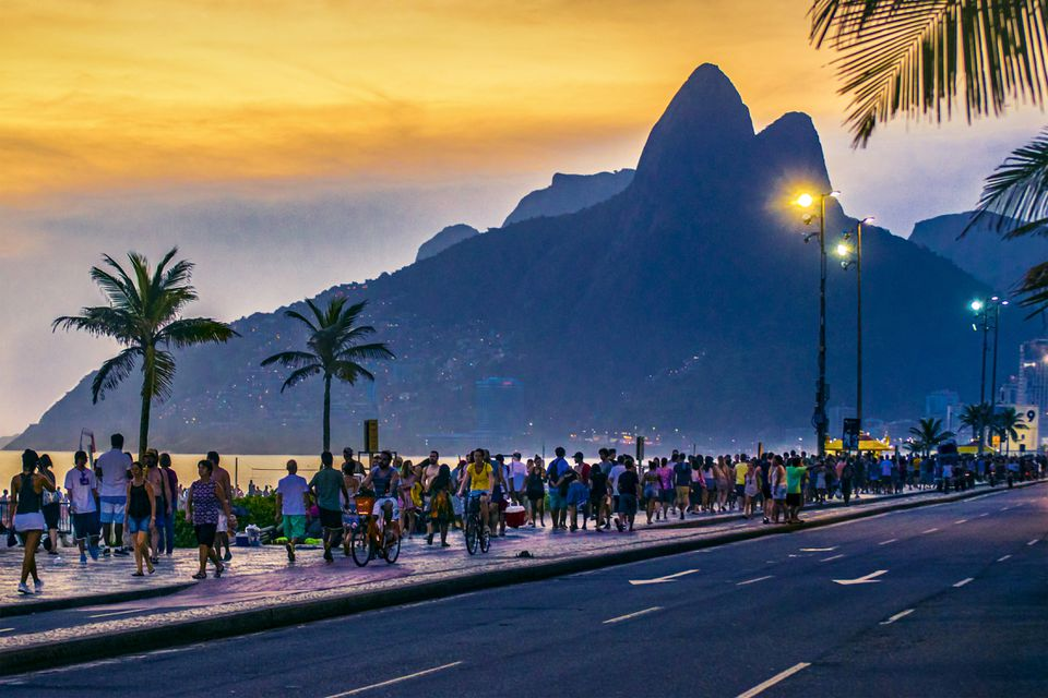 People On Road Against Sky During Sunset with the mountains of Rio de Janeiro in the background
