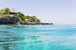 Jamaica, Negril, Traditional huts on rocky coastline