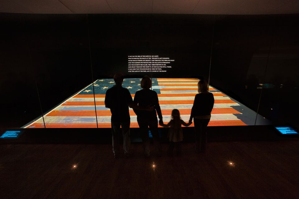 A family views the Star Spangled Banner at the National Museum of American History