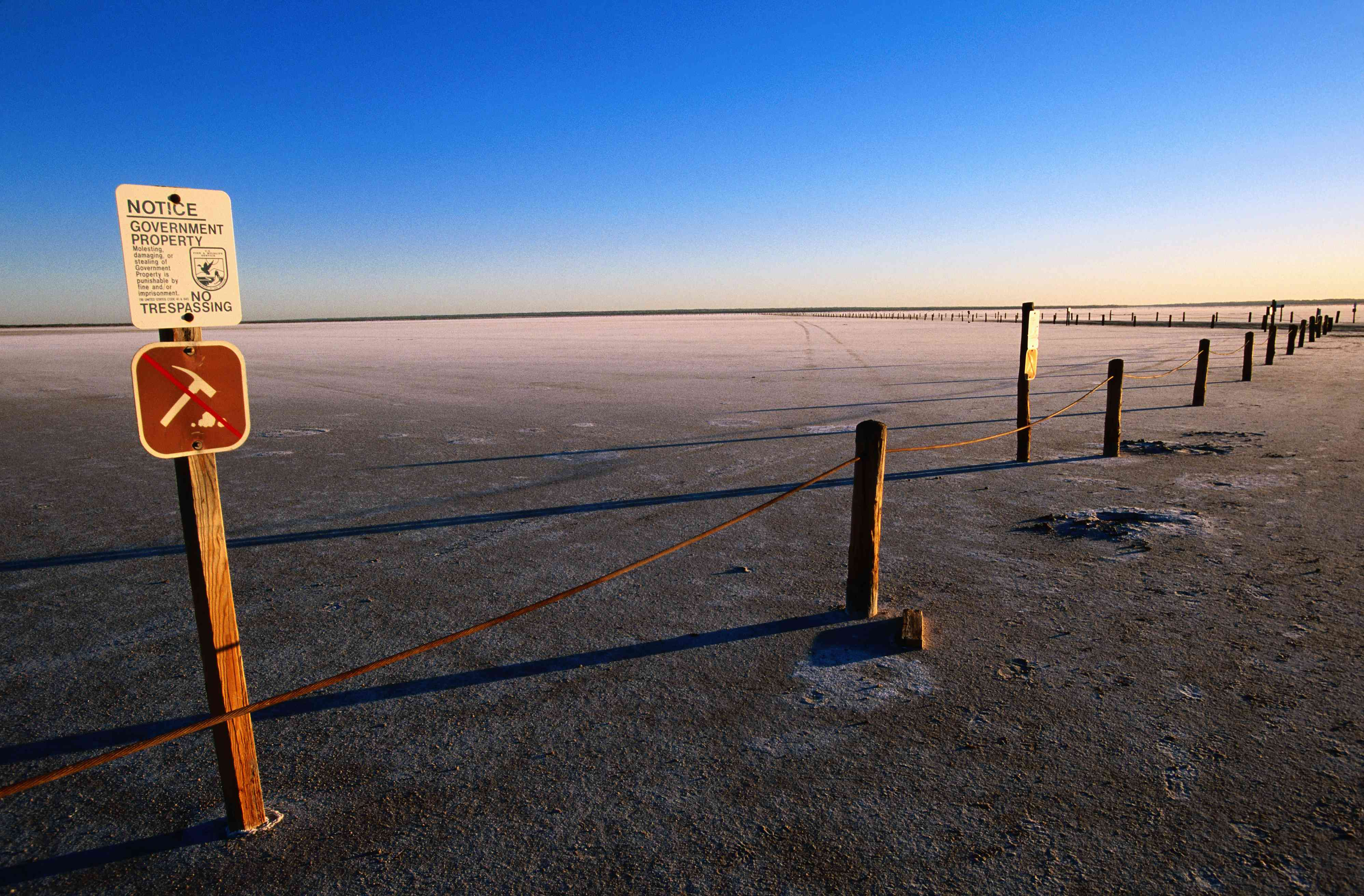 Salt flats with signs and posts.