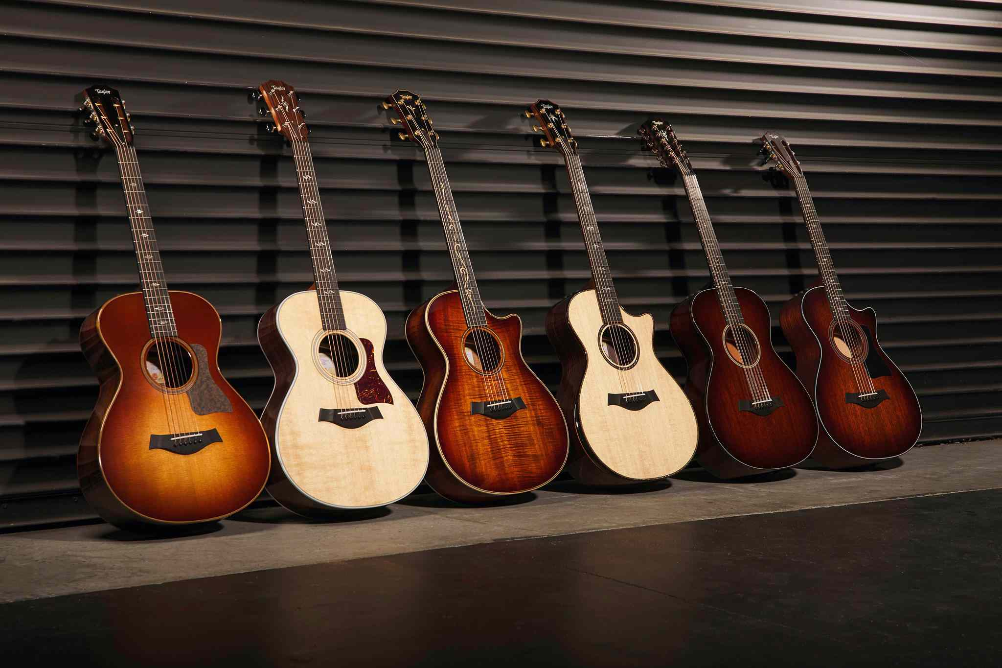 Row of six acoustic guitars leaning against a wall