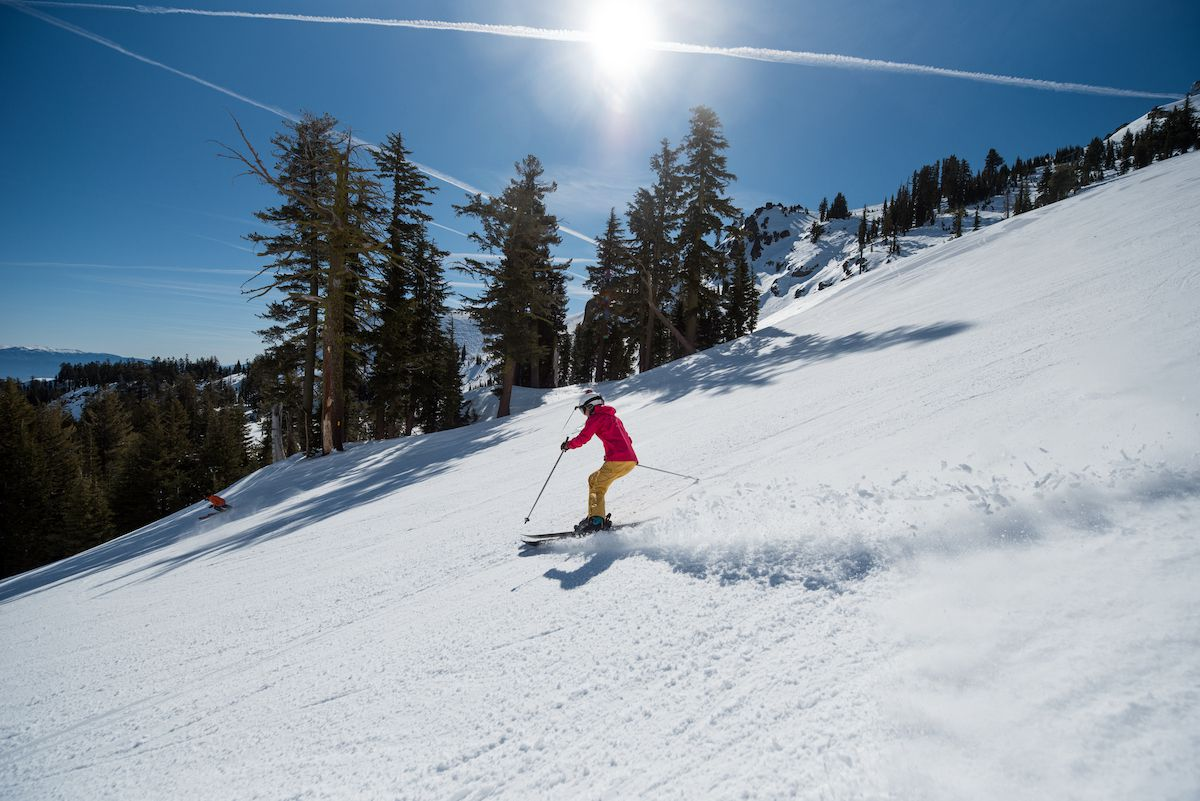 A skier soaks up the sun on a descent down a snowy slope
