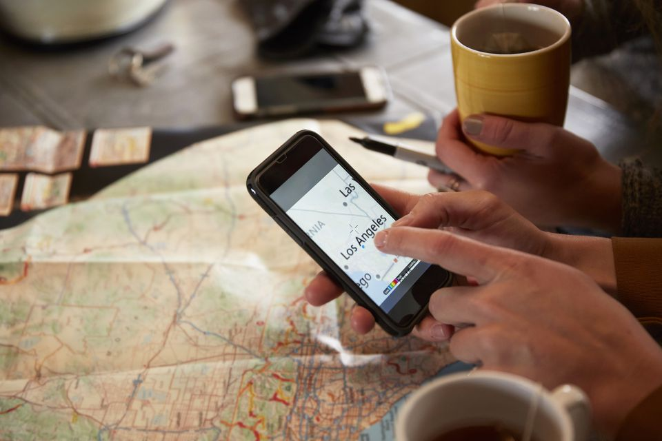 Planning road trip with phone and paper map