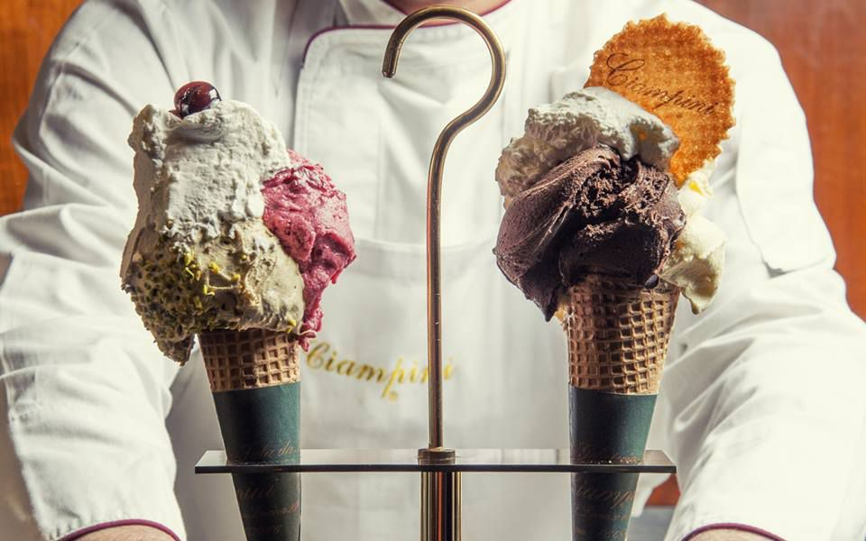 Person in chef's jacket holds two cones of gelato
