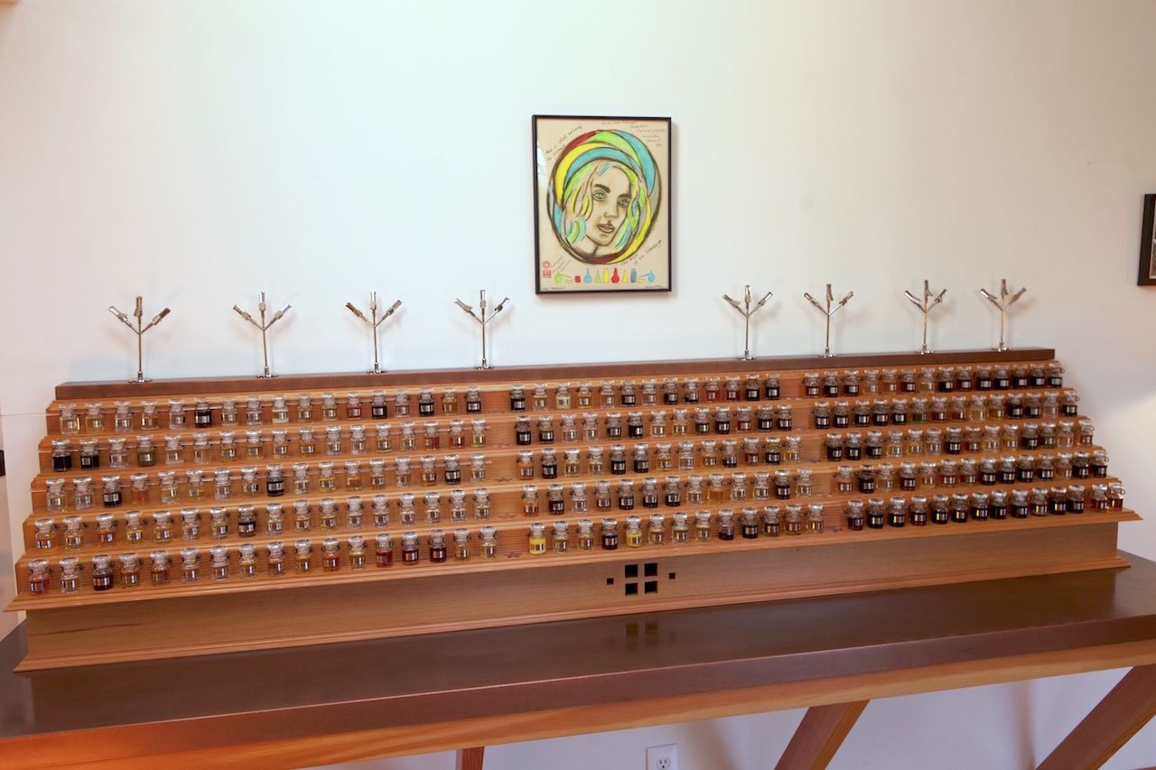 Dozens of small perfume vials arrange neatly of a wooden stage with five levels. Abover the structure is a small, colorful portrait of a woman