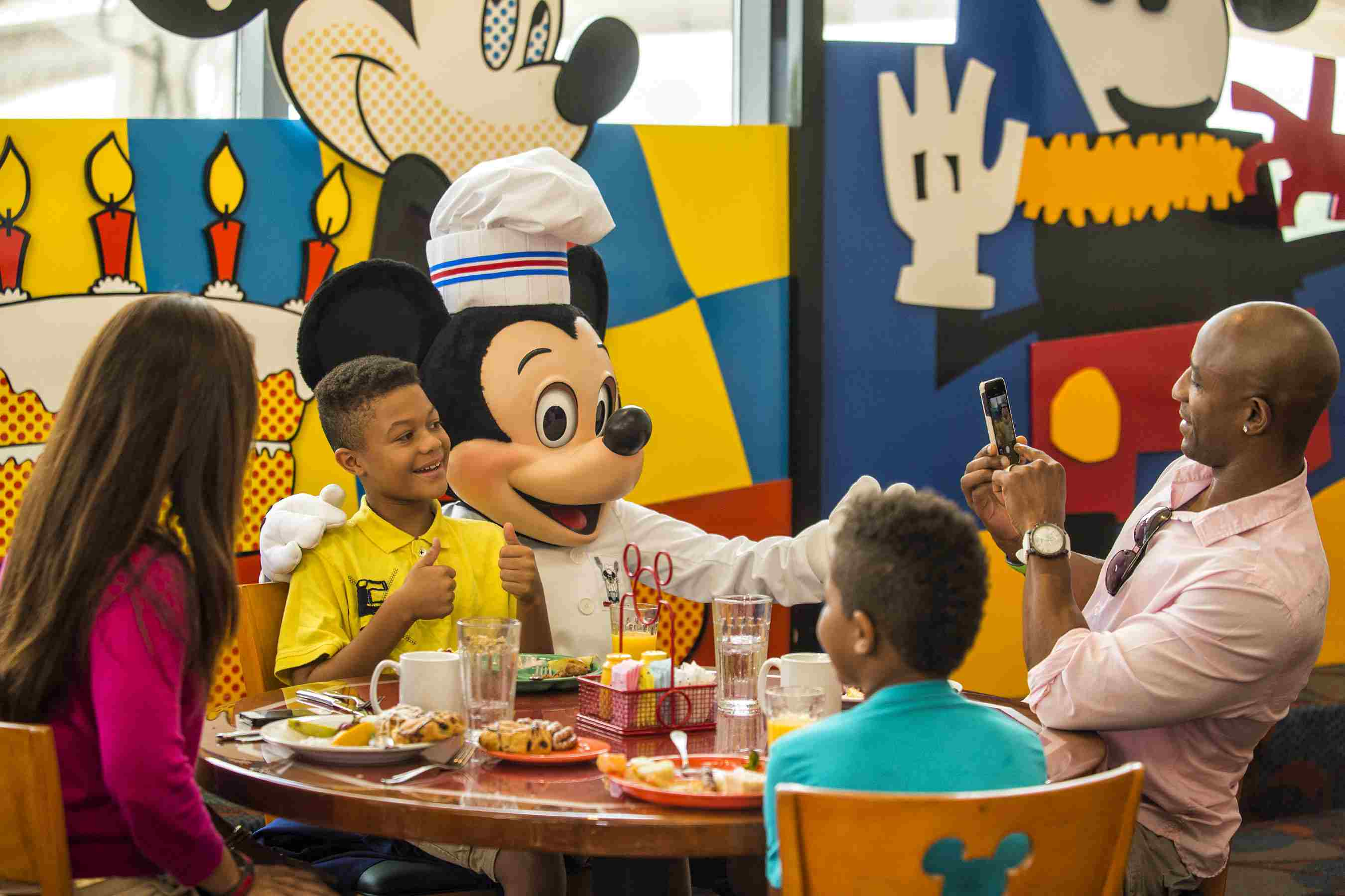 Mickey Mouse posing for a photo with a boy at a Disney character dining experience