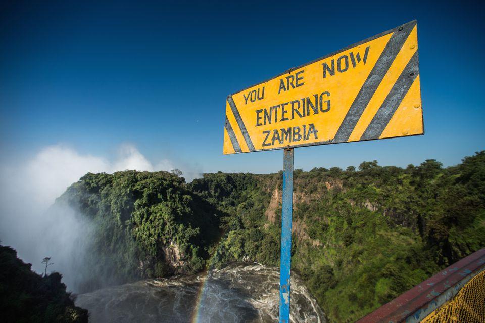 Sign marking the land border between Zambia and Zimbabwe at Victoria Falls