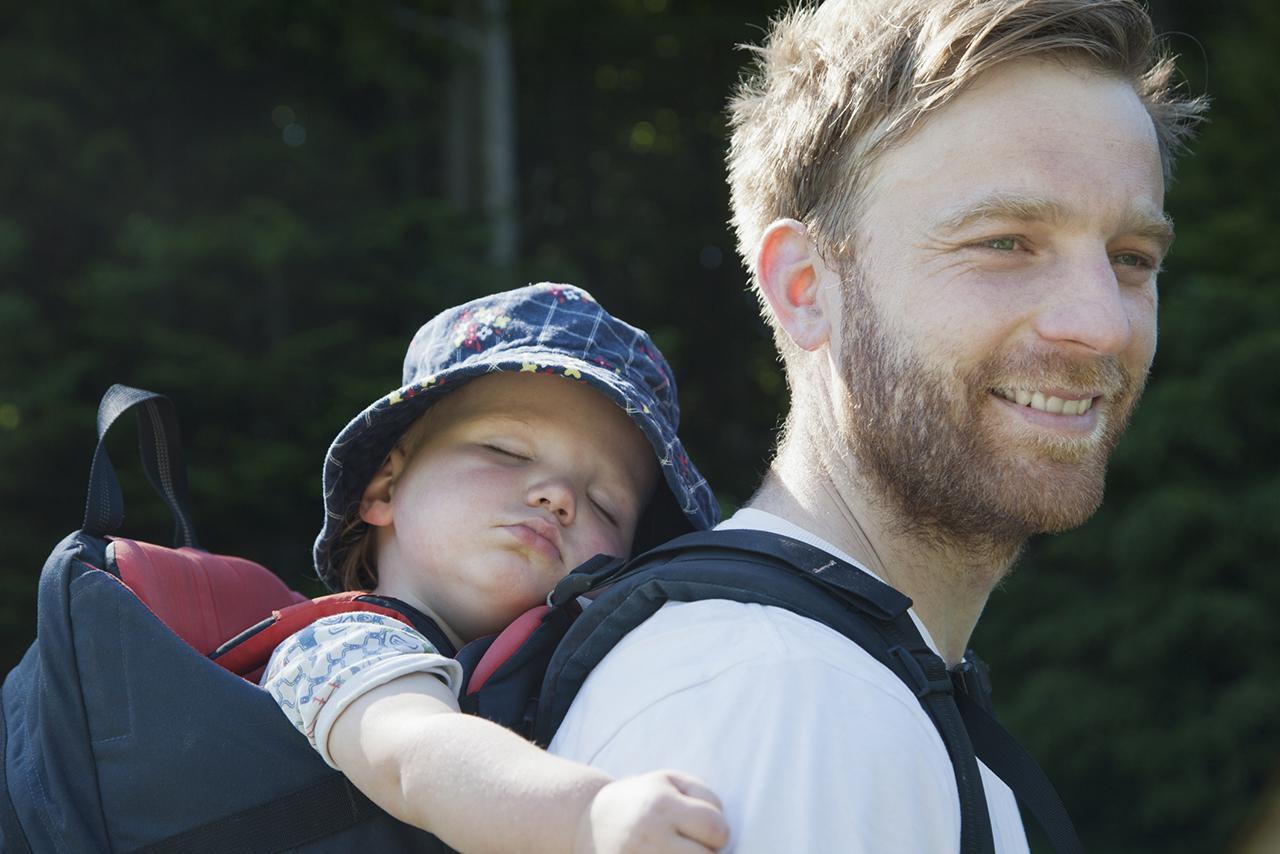 Padre llevando a su hijo en portabebés