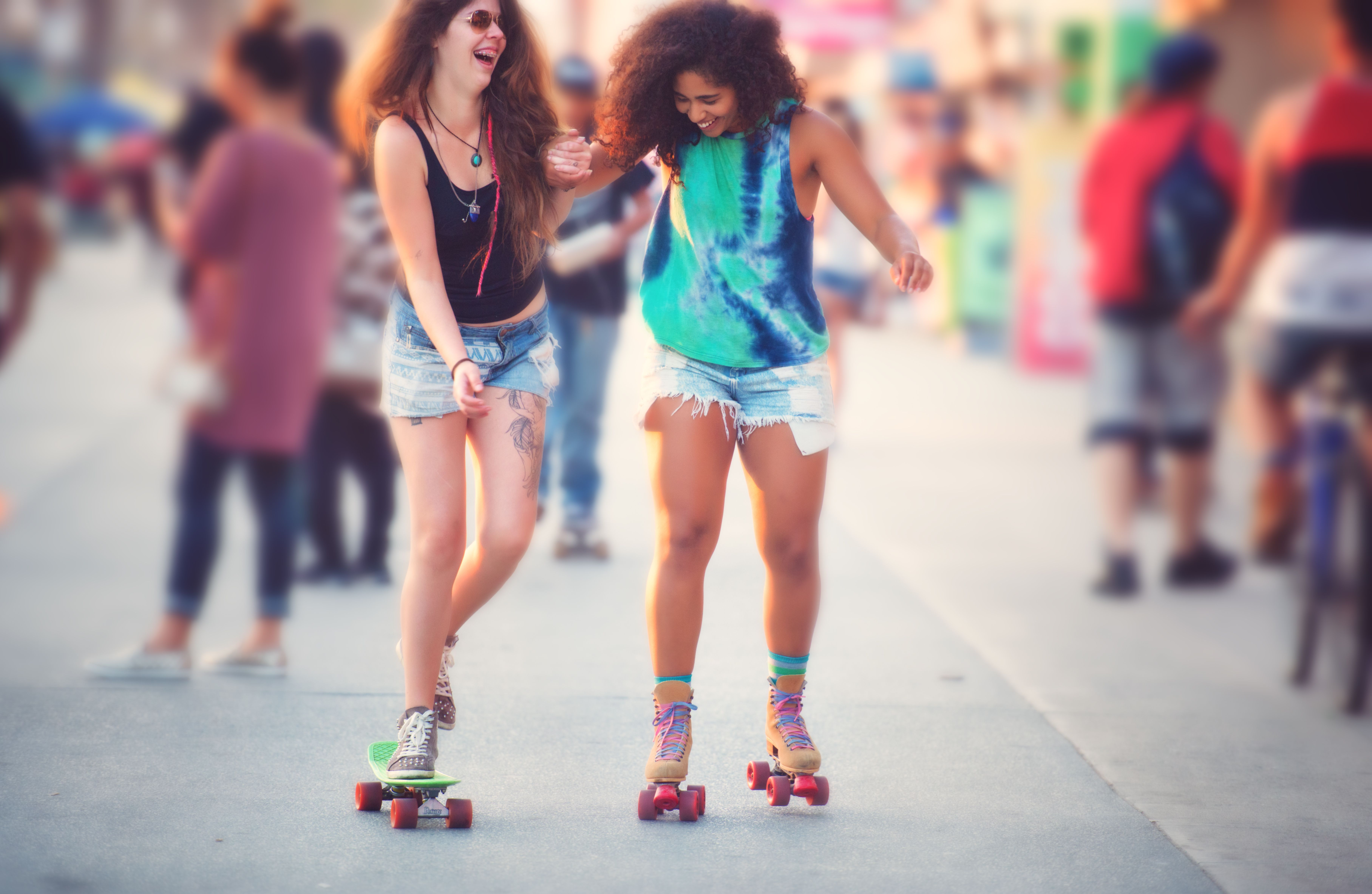 A laughing young woman attempts to learn skateboarding on the Venice Beach boardwalk with her girlfriend's help.