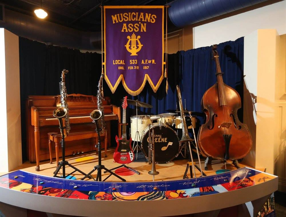 Small performance stage with drums, a piano, horns, a guitar, and an upright bass. There is a purple and gold banner above the stage that read