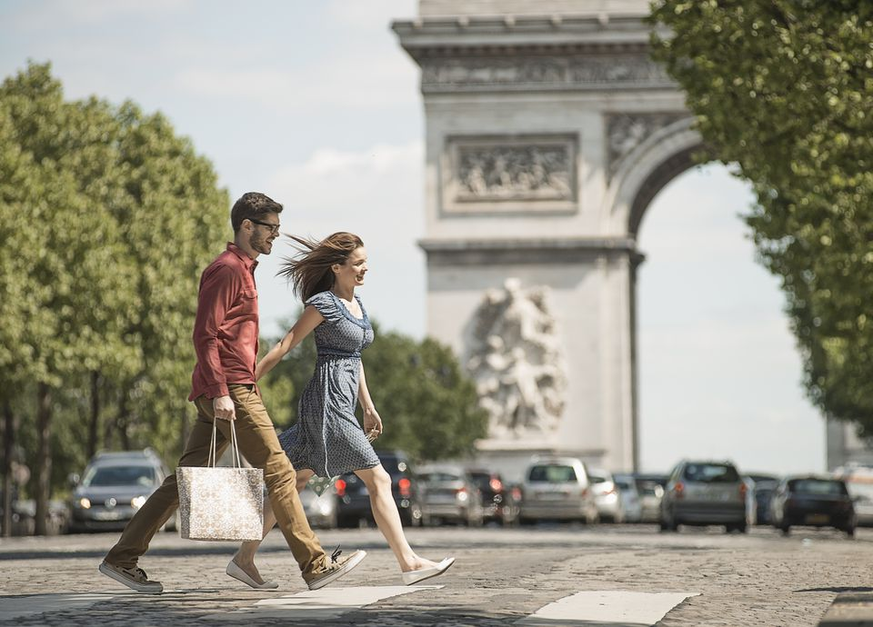 A couple strolling with their purchases in front of the Arc de Triomphe, Paris, France.