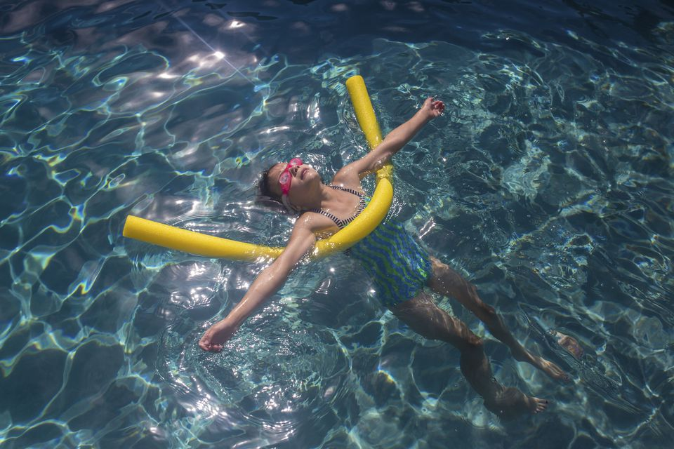 High angle view of girl with inflatable tube swimming in pool