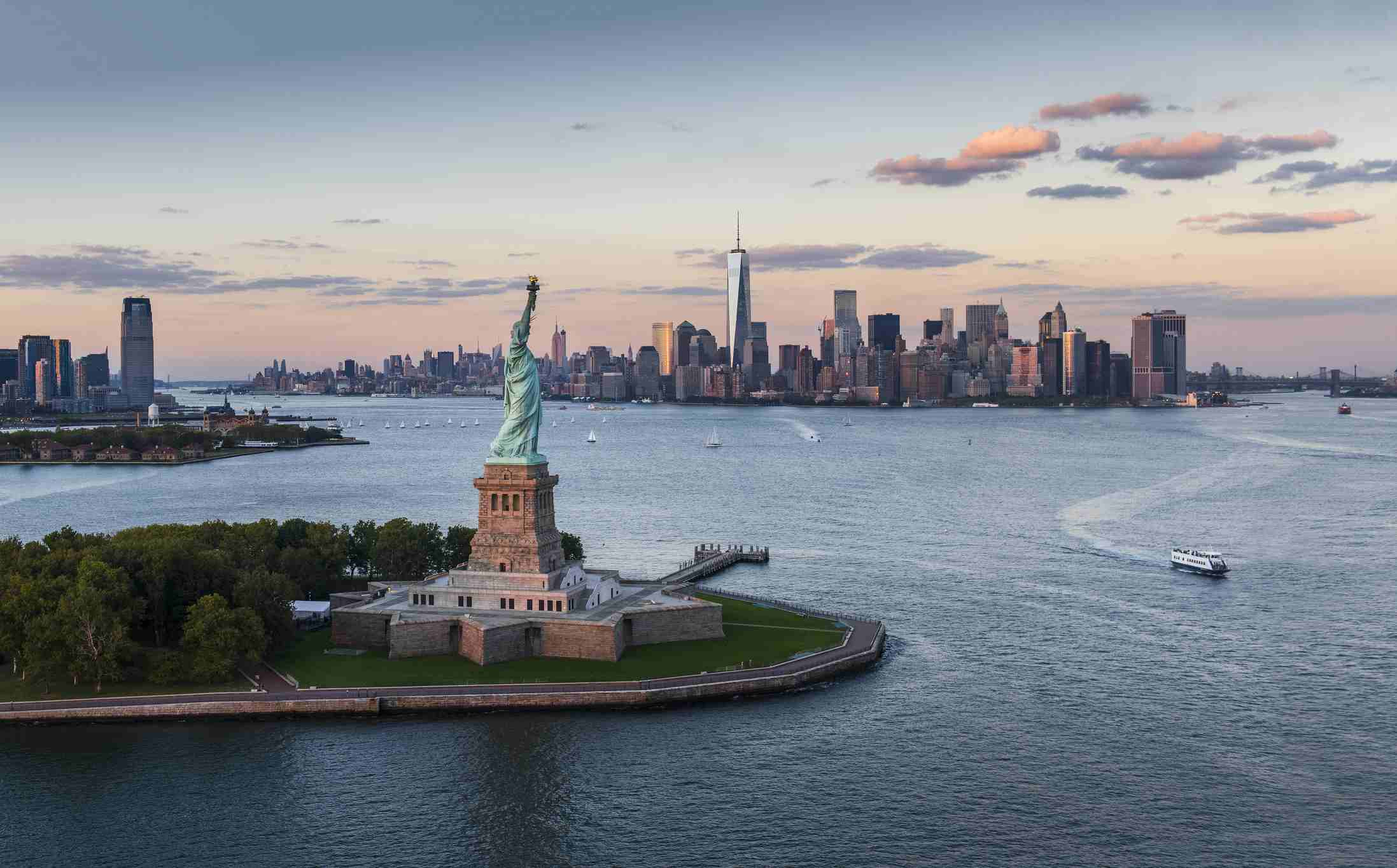 Aerial view of New York City with Statue of Liberty at sunset