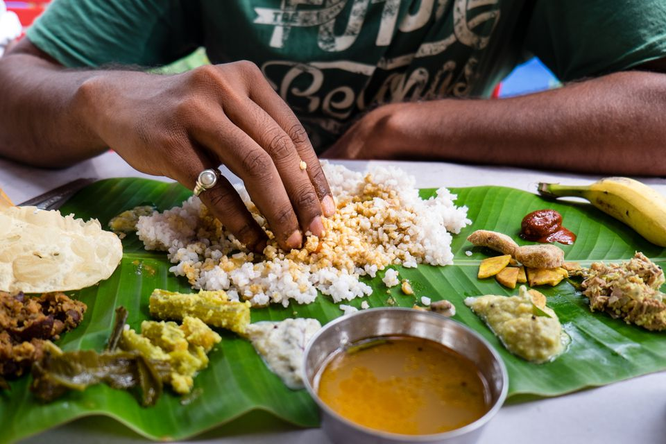 A Kerala Sadya, typical Keralite vegetarian dish served on banana leaf, eaten with fingers.