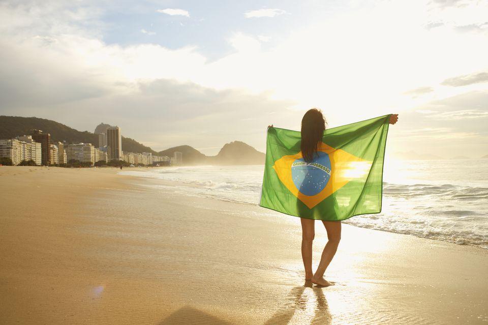 Mujer sosteniendo la bandera brasileña en la playa de Copacabana, Río, Brasil