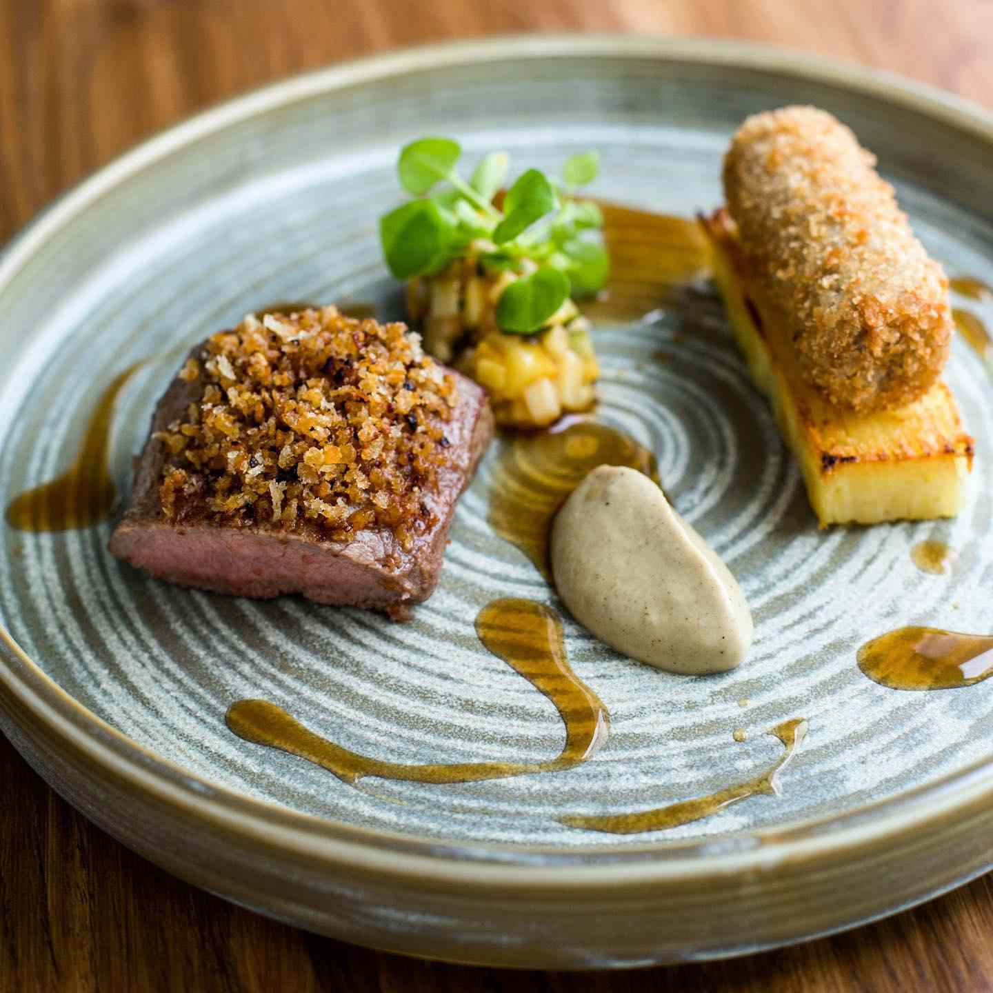 Plate of lamb loin and crispy lamb shoulder served with vegetables and sauces with artful plating