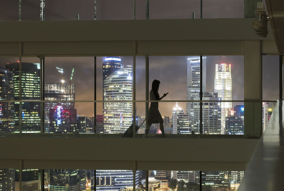 Young woman using smartphone and pulling suitcase, China skyline in view