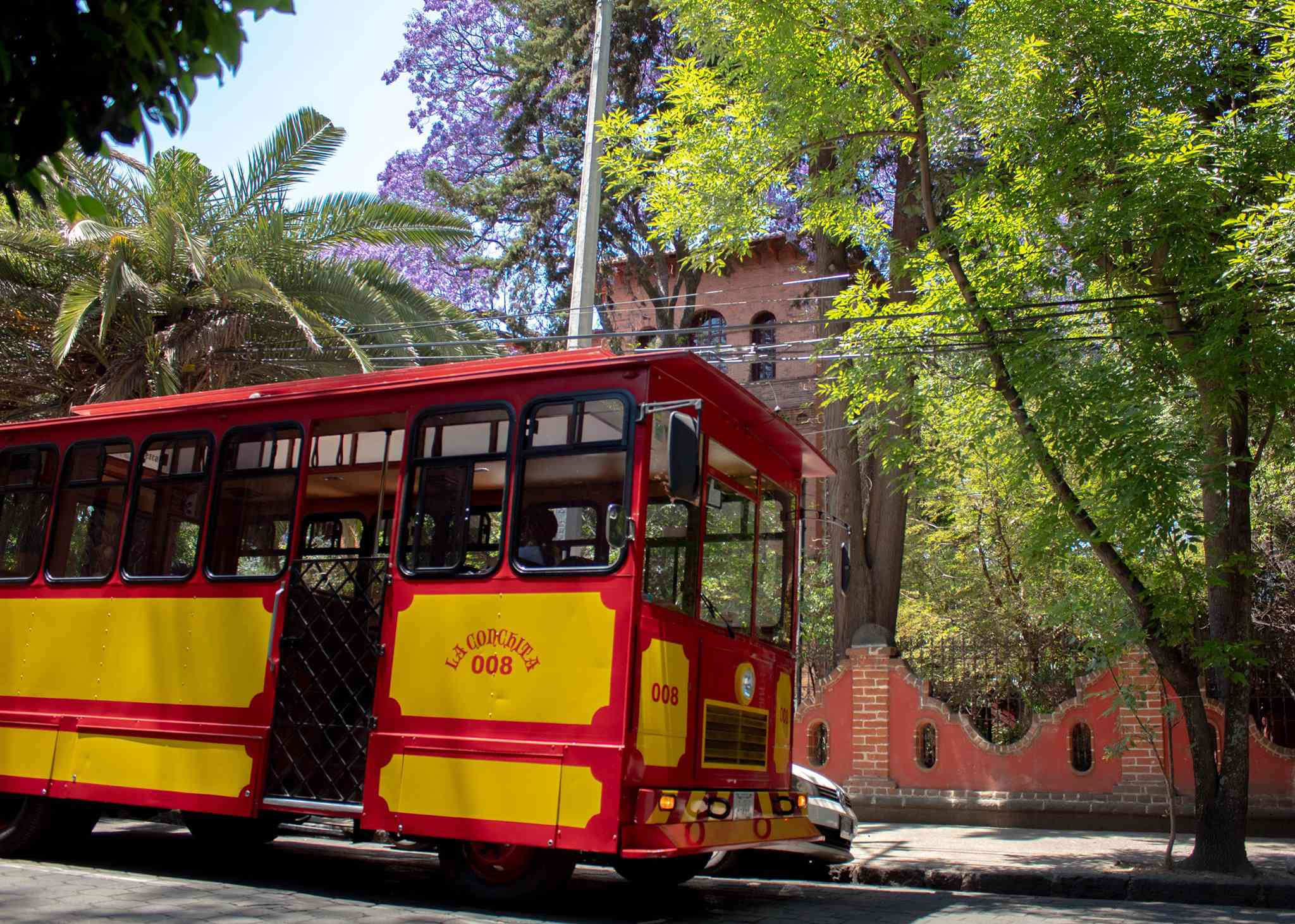 red and yellow Tourist Trolley in Coyoacan