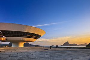 white spaceship-like buildings with large windows at sunset with the brazilian sugarloaf mountians in the background