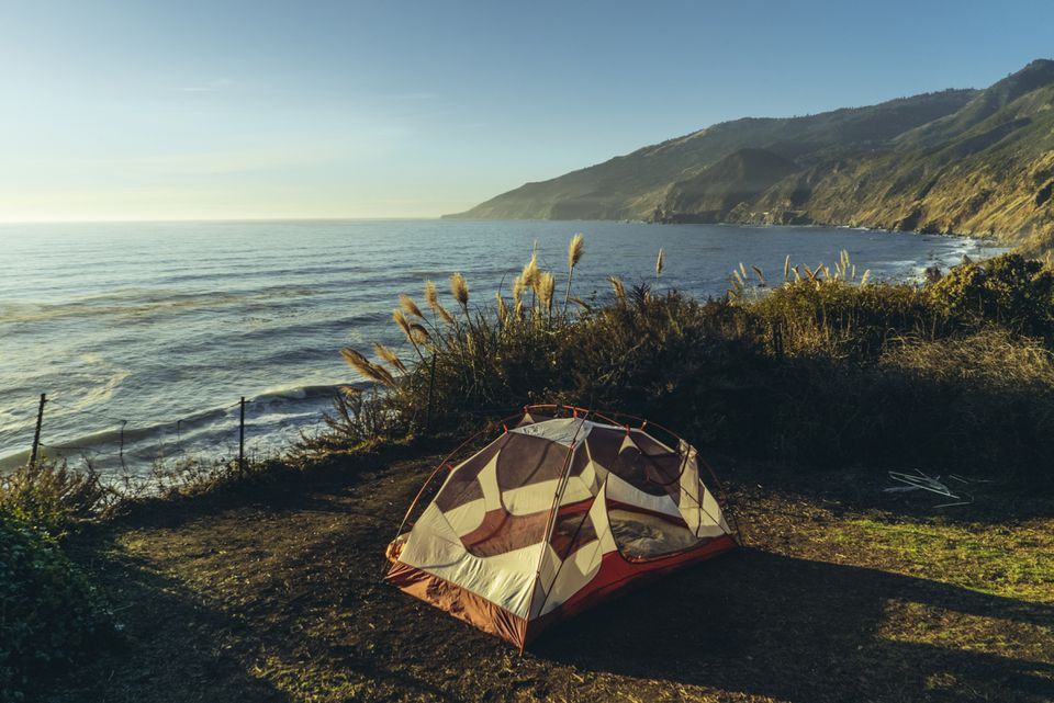 Tent on field by sea during sunset