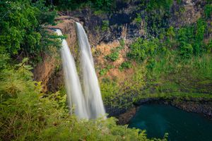 Wailua Falls, in Kauai, Hawaii with green mossy on a cliffside