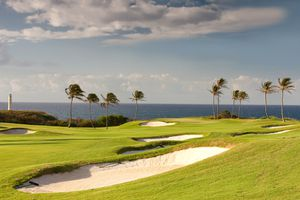 The Ocean Golf Course with palm trees at the edge of the course and the ocean in the background on Kauai