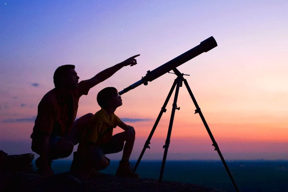 Father and son looking through telescope at dusk
