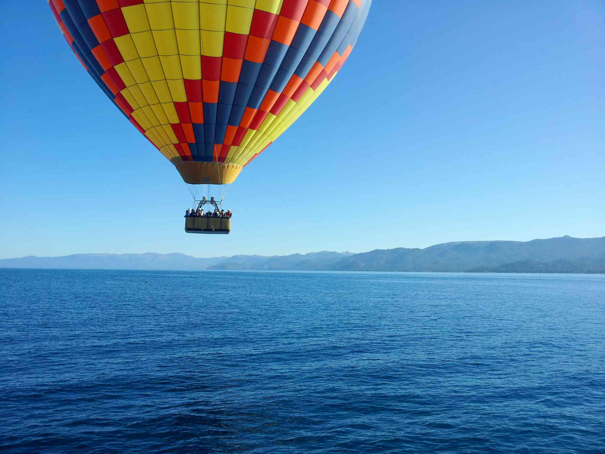 A colorful hot air balloon floating above Lake Tahoe in California