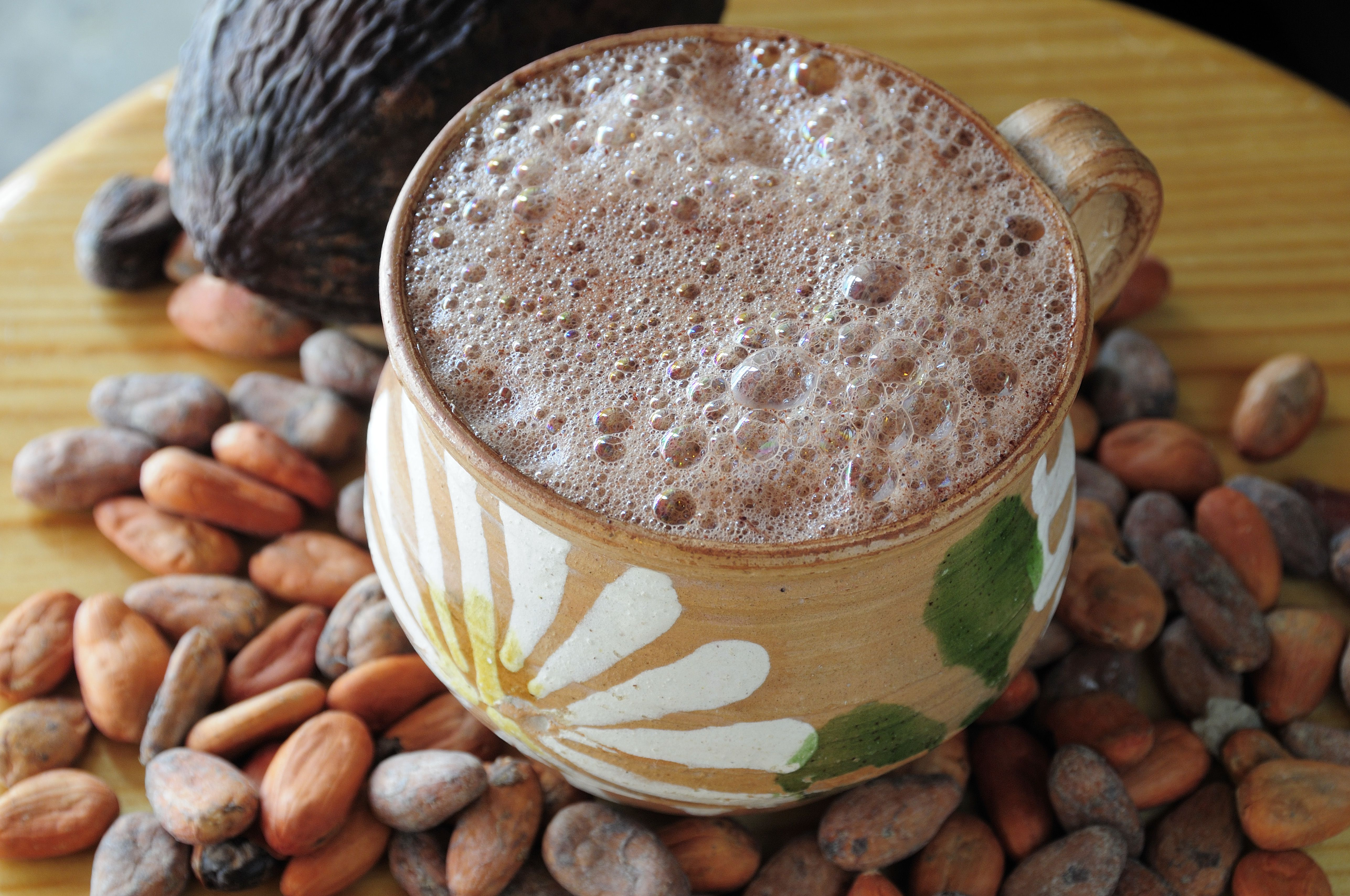 Mexico, Oaxaca, Chocolate caliente, hot chocolate in painted cup with cocoa beans and pod