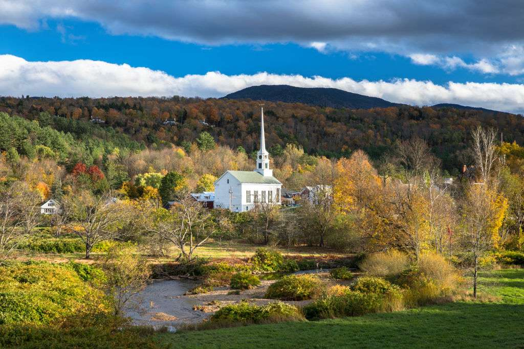 white church with a steeple in a field of autumn trees