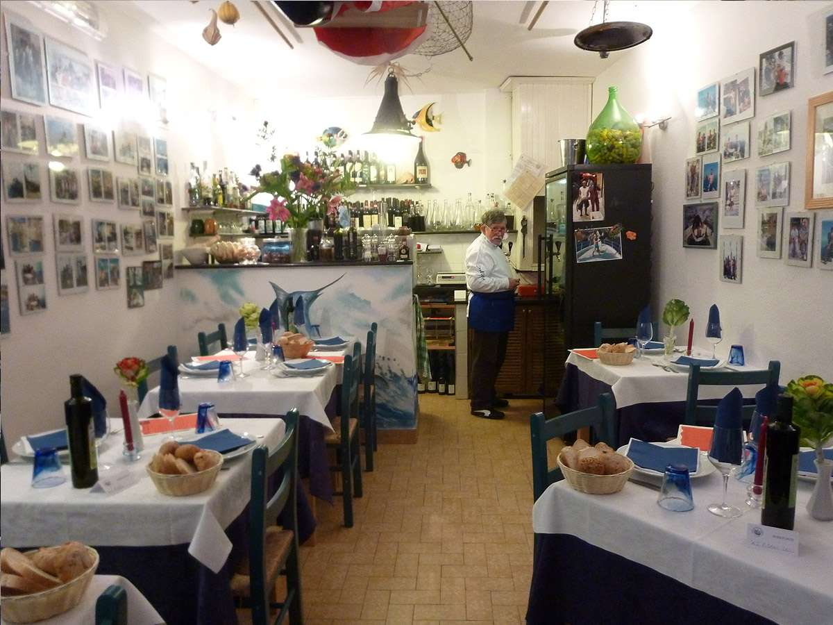Man standing at the back of a small restaurant with photographs on the wall